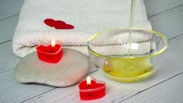 Das Konzept eines Spas am Valentinstag. Eine Kosmetikerin gießt Massageöl in eine Schüssel. Vorbereitung des Kosmetikbüros für Entspannungs- und Wellness-Sitzungen. Badeverfahren, Kosmetologie