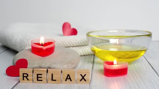 Koncept lázní na Valentýna. Svíčky ve tvaru červeného srdce, kameny, masážní olej, uvolnění slov a bílý ručník na dřevěném pozadí. Relaxační a wellness péče. Koupel, kosmetika