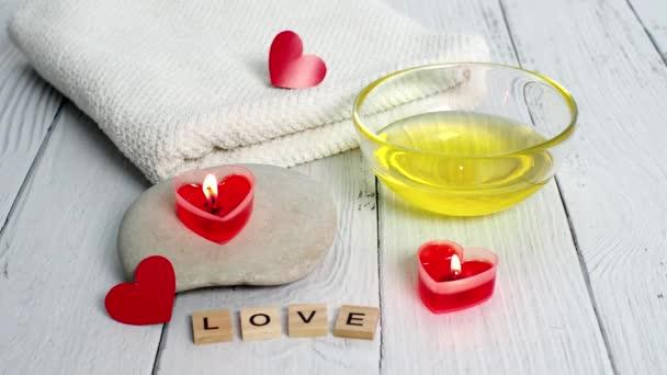 Koncept lázní na Valentýna. Svíčky ve tvaru srdce, kameny, masážní olej, slovo láska a bílý ručník na dřevěném pozadí. Relaxační a wellness péče. Koupel, kosmetika