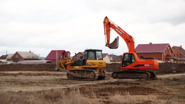Crawler loader excavator, bulldozer and roller work on construction site. Machines perform excavation work. Compaction of soil and rubble for residential buildings. Volgodonsk, Russia 10 March 2020.