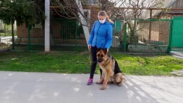 Dívka v ochranné lékařské masce chodí se psem po ulici a hladí zvíře. Volný čas s domácím mazlíčkem během karantény. Procházka s německým ovčákem na čerstvém vzduchu. Sebeizolace a ochranný režim.
