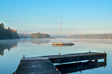 Morning autumn landscape. Wooden pier and boat on a beautiful lake.