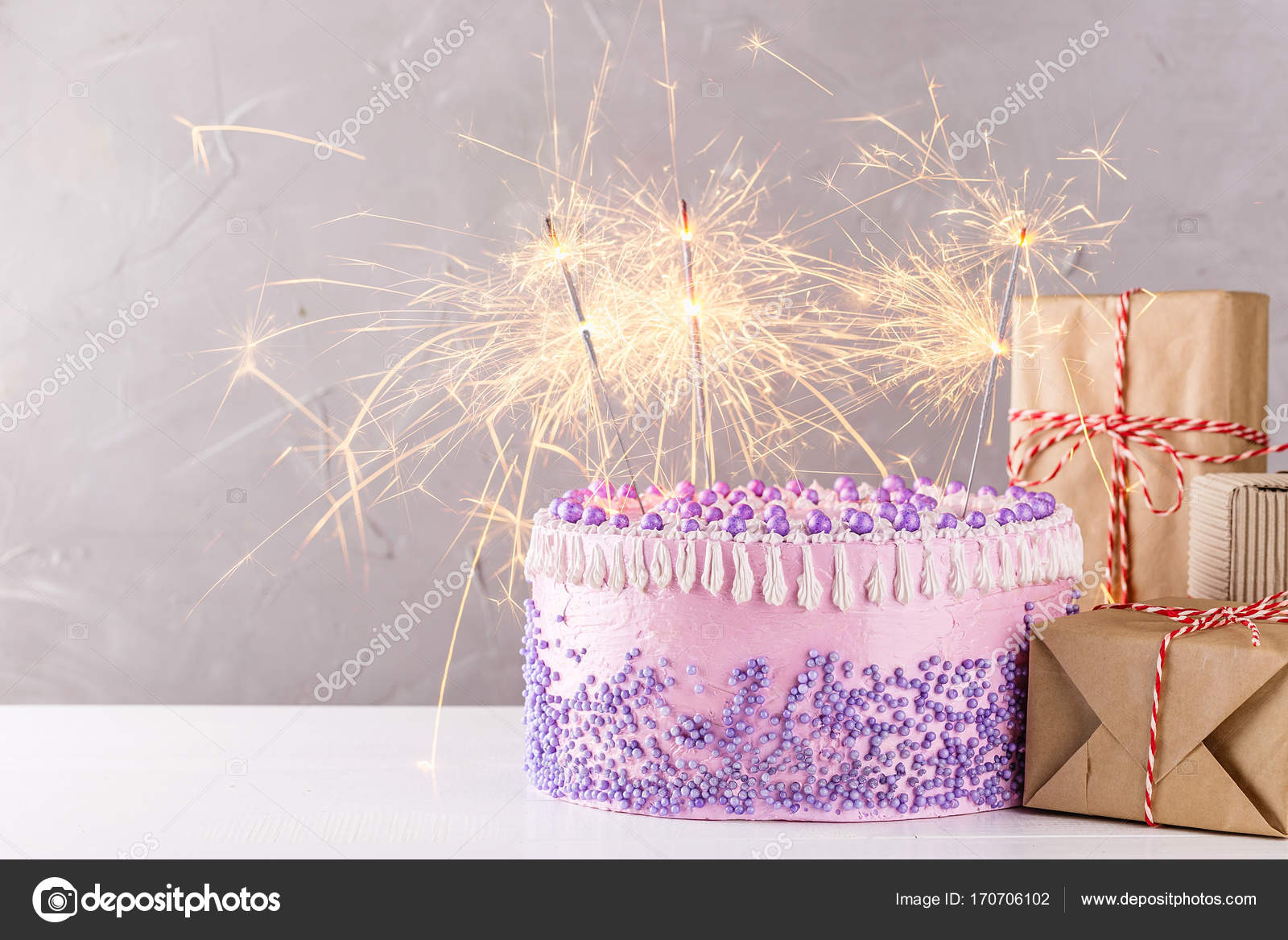Pink Birthday Cake With Sparklers And Gift Boxes Stock Photo