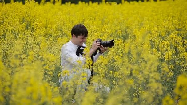Fotografo con una fotocamera di scattare foto in un campo di fioritura giallo