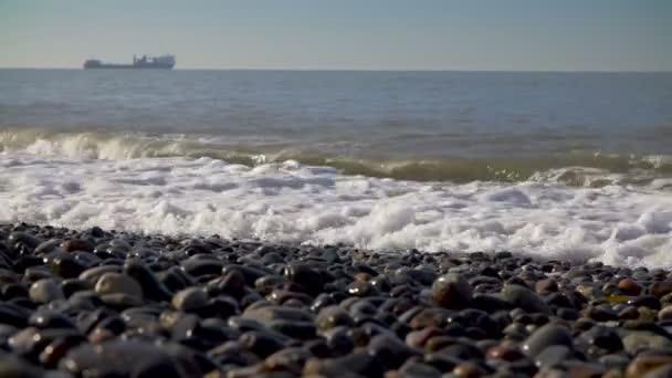 Přílivová vlna na pobřeží moře kamenité, oblázkové