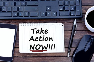 Take action Now words on notebook