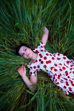 brunette in a bright dress lying in the tall grass