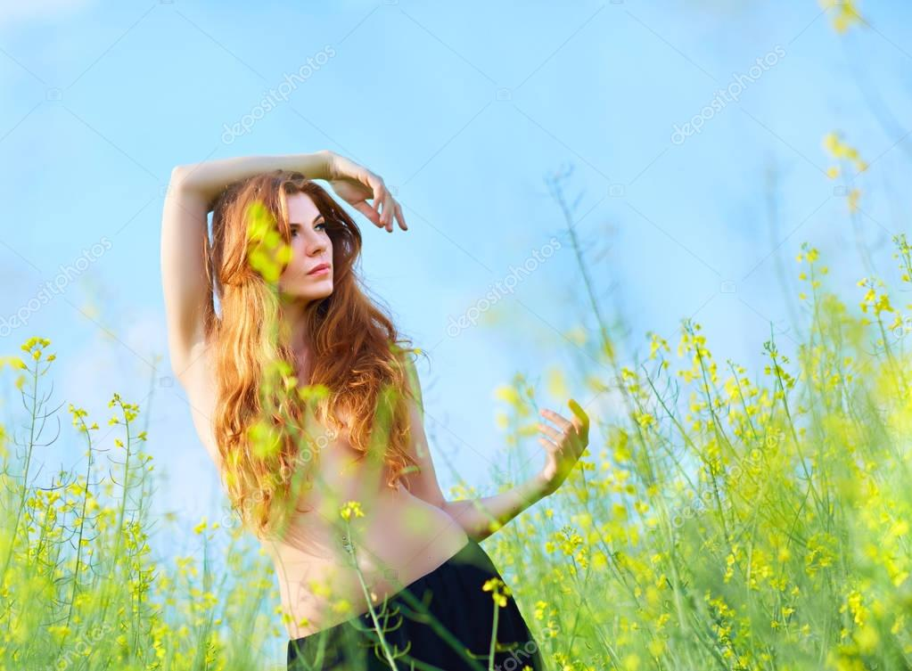 red-haired girl in a rapeseed field