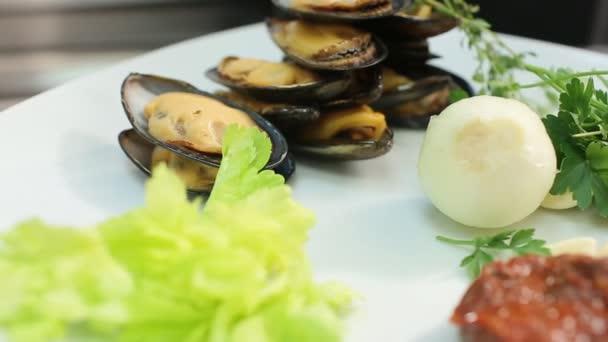 leckeres Gourmetgericht mit Miesmuscheln, Knoblauch, Zwiebeln und Salatblättern auf weißem Teller