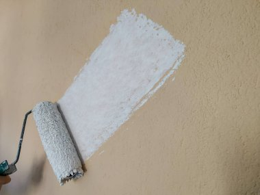 Man hand holding paint roller and painting the wall from orange to white color with visible contrast, while renovating and house restoration