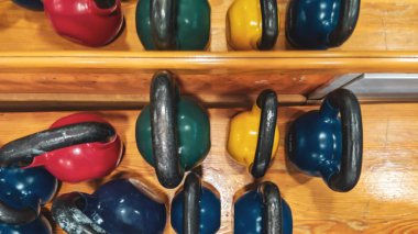 Top view of kettlebell dumbbells in different colors and weights stacked as part of gym equipment ready to be used for bodybuilding and weightlifting