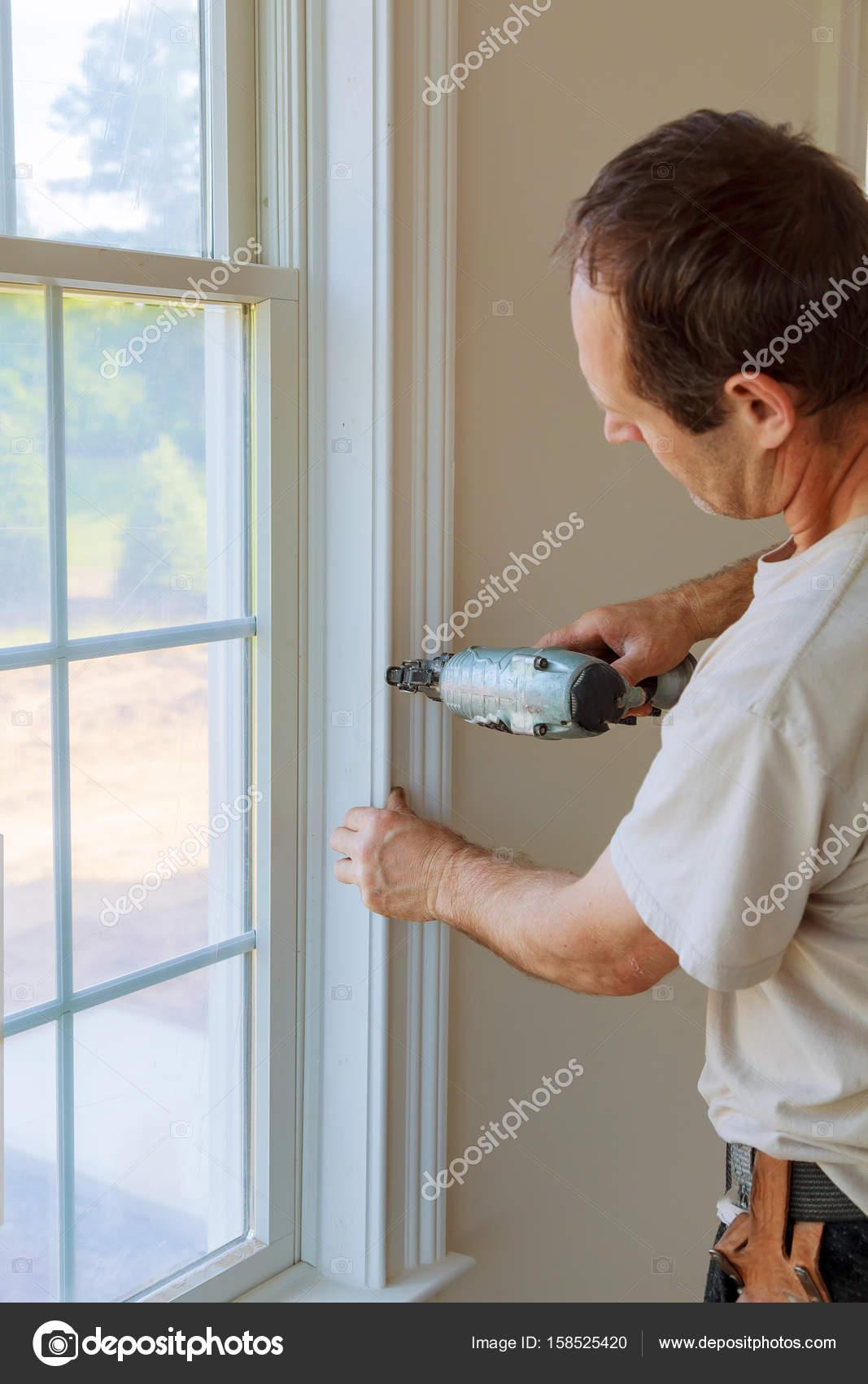 Brad mit Nagelpistole an Formteilen unter Windows, framing Trim ...