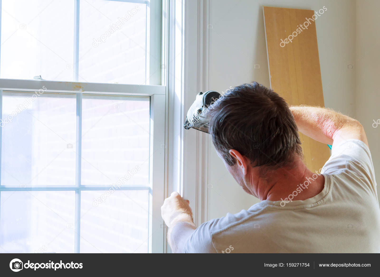 window framing trim cottage style window carpenter using nail gun to moldings on windows framing trim with the warning that all power tools have them shown illustrating safety concept photo trim