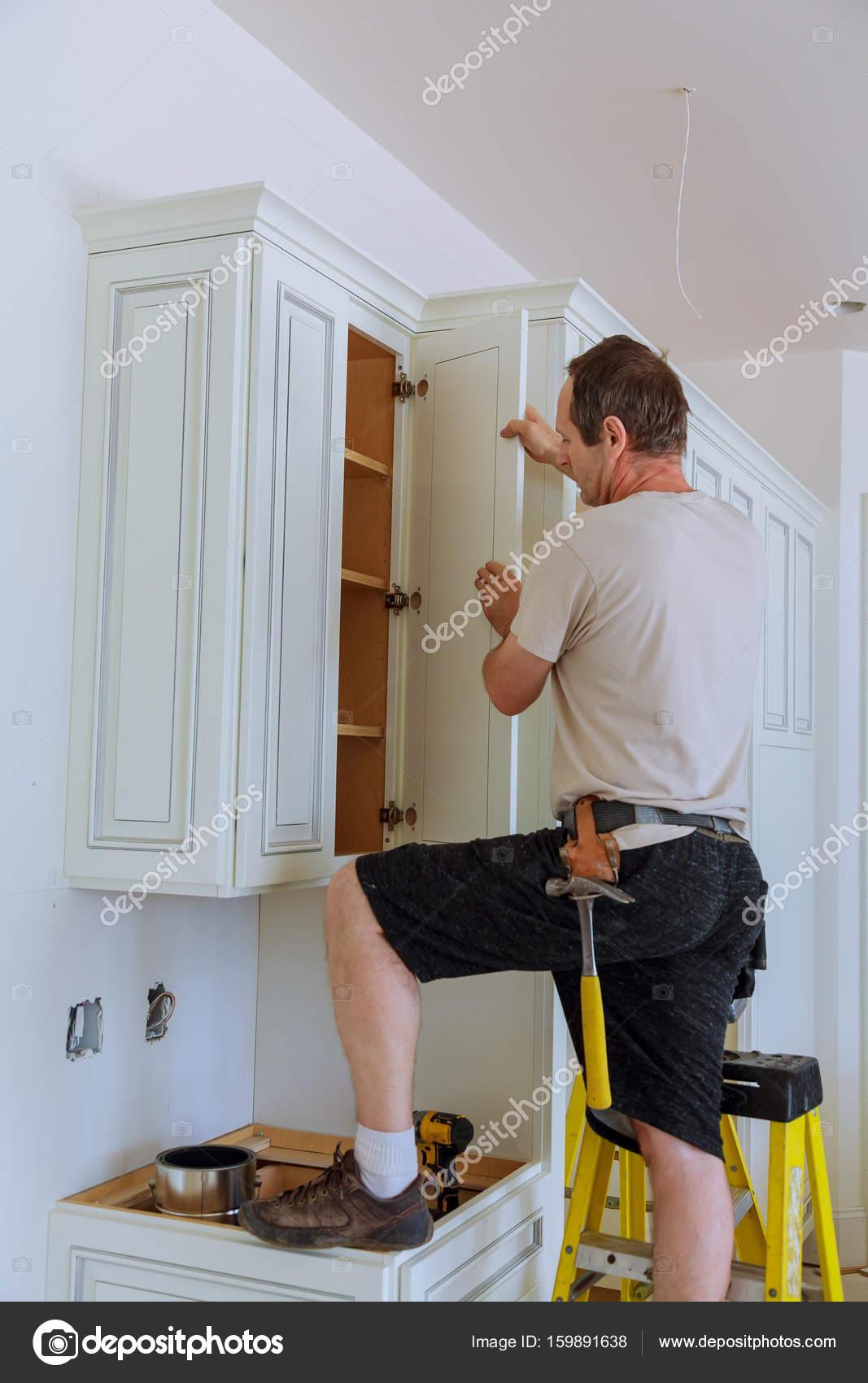 Einbau Küche. Arbeiter installiert Türen auf Küchenschrank ...