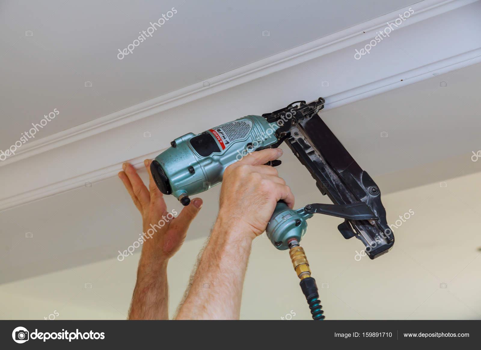 Carpintero de brad con pistola de clavos a la estructura de la ...