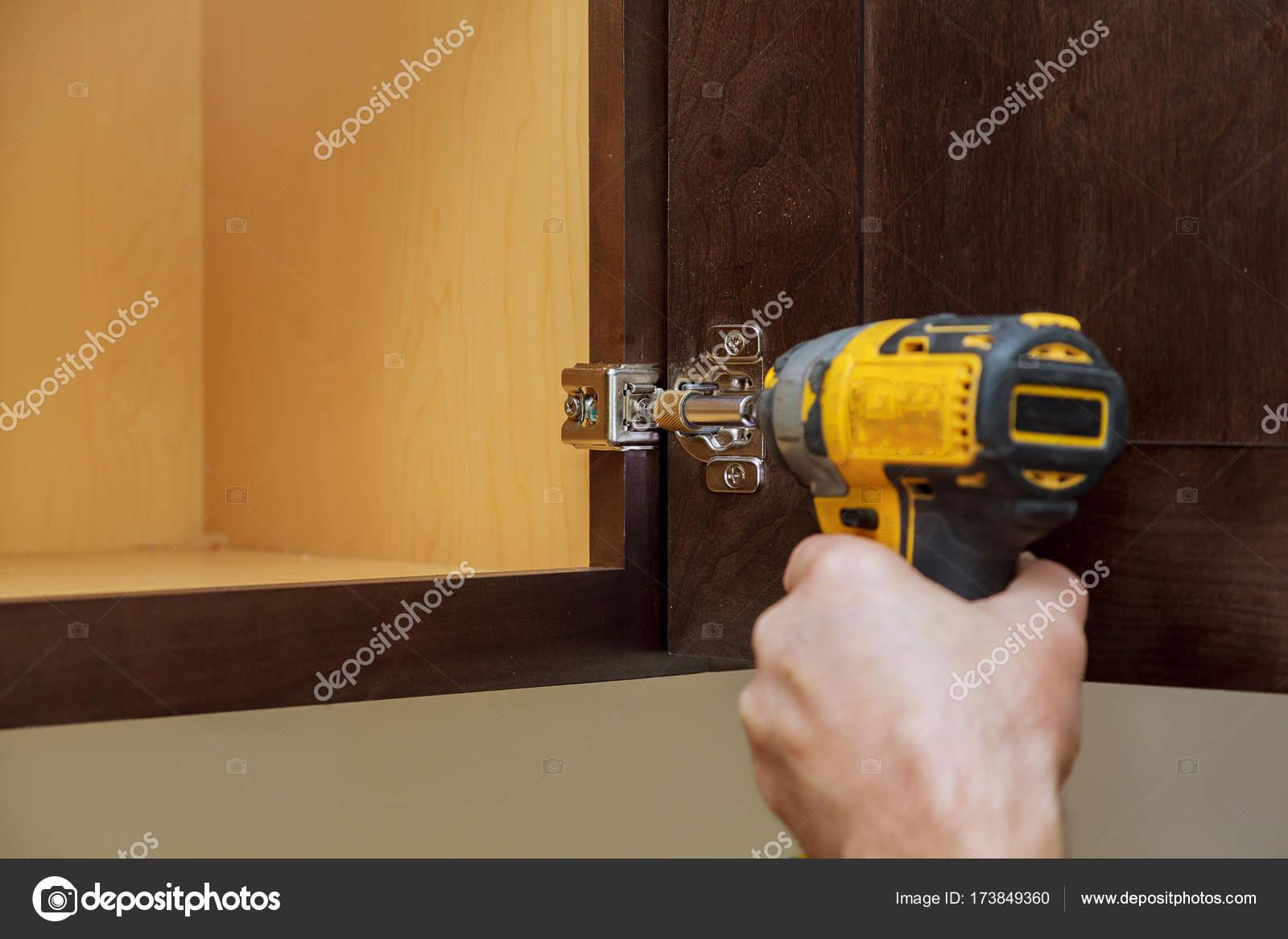 Workman behebt ein Scharnier, ein Küchenschrank — Stockfoto ...