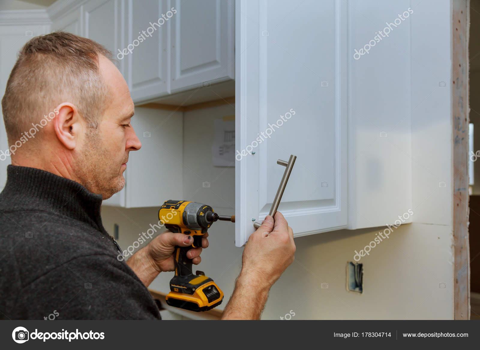 Montage der Türgriffe auf Küchenschränke mit einem Schraubendreher ...