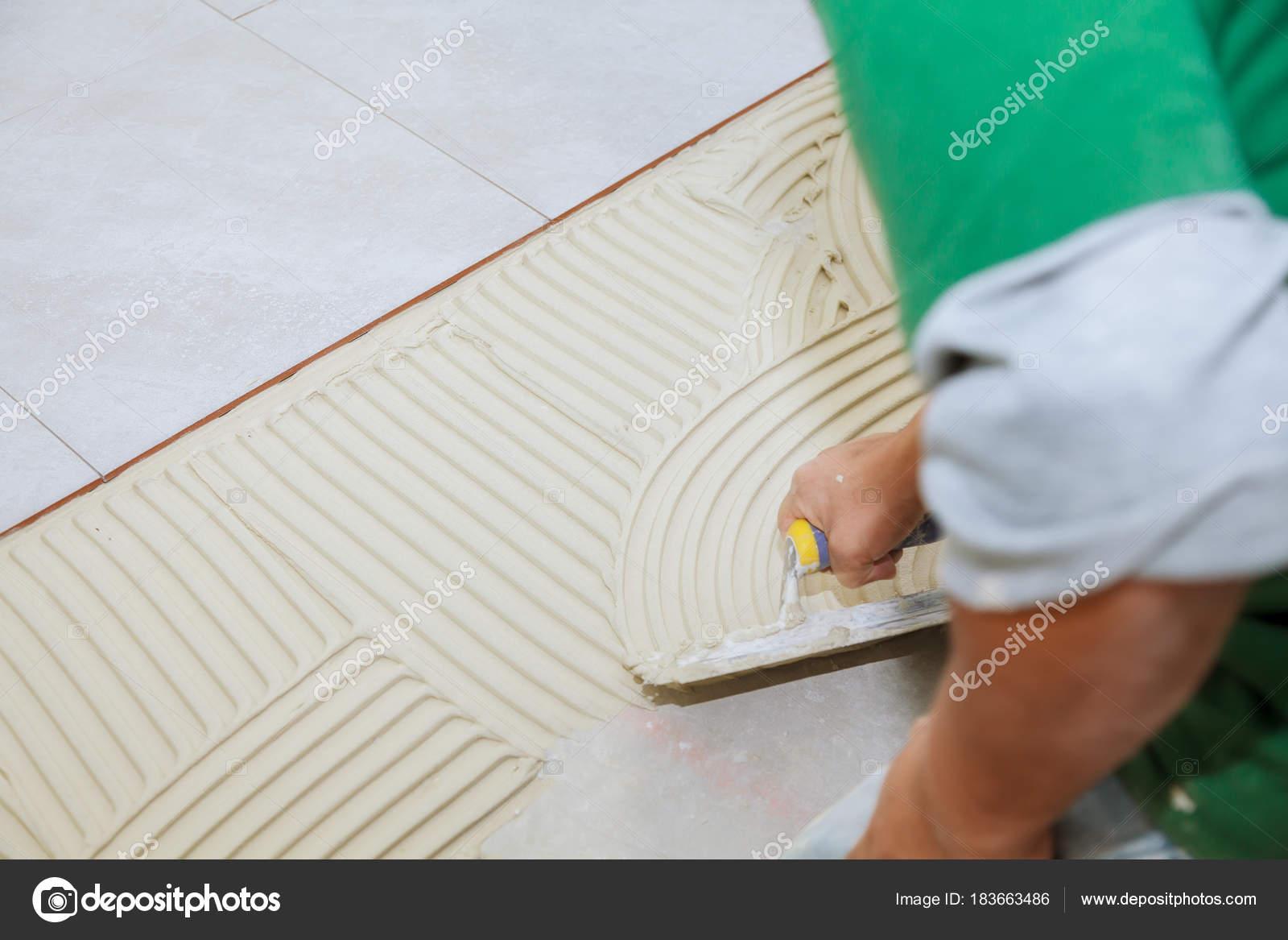 Operaio installa piastrelle sul pavimento ha messo la colla con