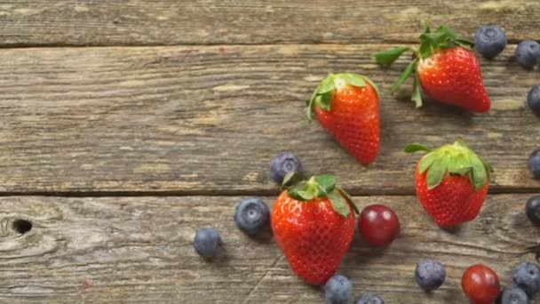 summer fruits on a wooden table. Blueberries Grape Strawberries SLOW MOTION hd video