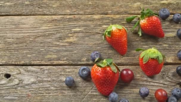 nyári gyümölcsök egy fából készült asztal. Áfonya szőlő eper lassított hd videó