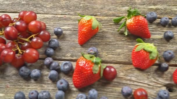 tasty summer fruits on a wooden table. Blueberries Grape Strawberries Blackberries SLOW MOTION hd video