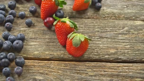 ingredients for a healthy Grape Strawberry Blueberries berries, fruit, and wooden background, top view, horizontal SLOW MOTION hd video