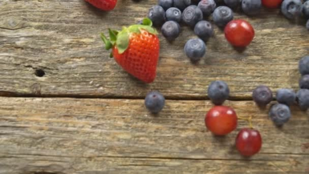 Fresh berries on wooden background Grape Strawberry Blueberries Organic Healthy Products SLOW MOTION hd video