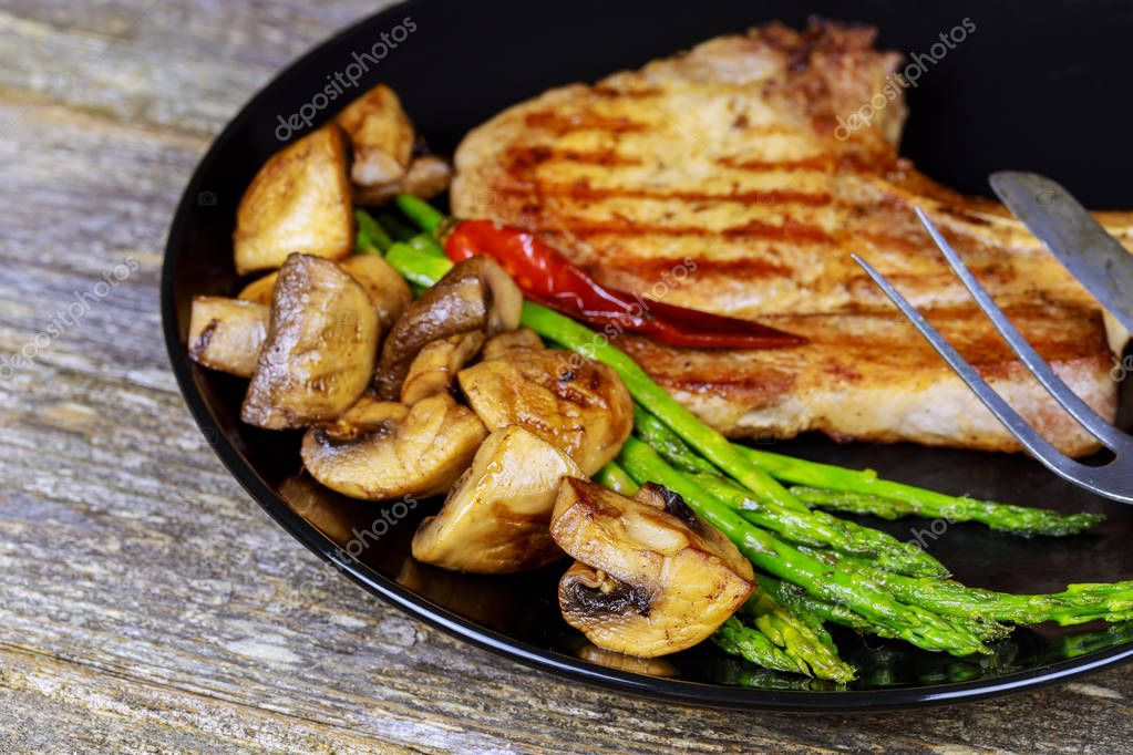 Grilled striploin steaks with mushrooms and green asparagus on a plate, selective focus,