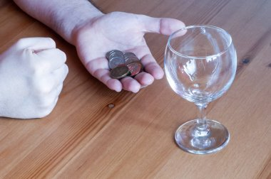 wine glass on table coins money spent on alcohol closeup hands c