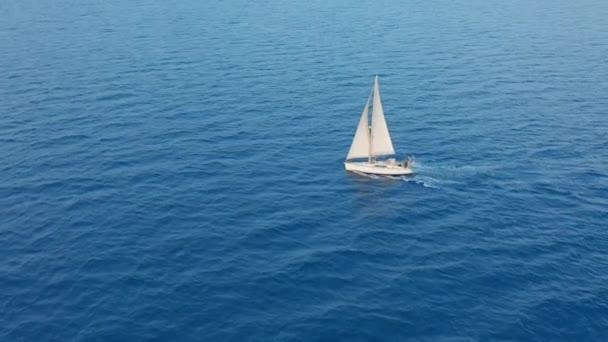 Légi kilátás jacht vitorlázás nyílt tengeren. Vitorlás jacht felülről. Yachting a szeles napon.