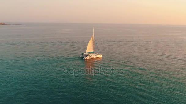 A jacht vitorla a tengerre a naplemente. Drone repül a hajó vitorlák körül. Katamarán vitorlák, naplementekor, videó a drone. Phuket sziget, Thaiföld.