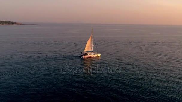 Jachta se plaví na moři při západu slunce. Dron létá kolem jachta s plachtami. Katamarán plachty při západu slunce, video z dron. Ostrov Phuket, Thajsko