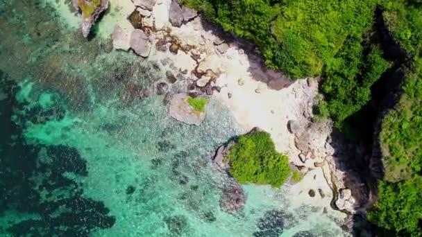 Egy gyönyörű öbölben, trópusi trópusi sziget, sziklák, a cape és a dzsungel légifelvételek. Hullámok break sziklás partján. Türkizkék lagúna. Paradicsom. Utazás és üdülési fogalom. Bali. Indonézia.