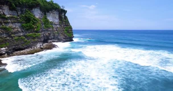Let podél krásného pobřeží, tyrkysové moře a vlny zřítilo na skalách. Surfaři zachytit vlny na útesu. Odpadky v moři. Bali, Uluwatu pláž.