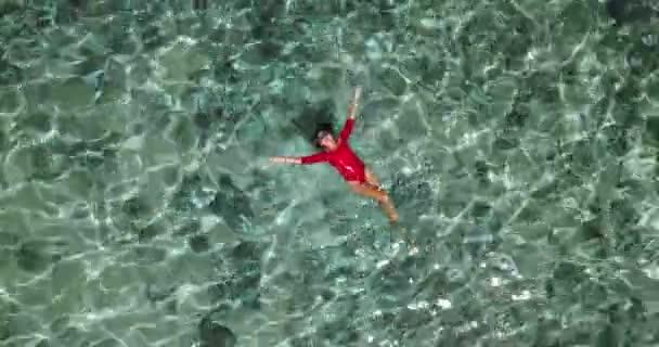 Immagine di estate di bella ragazza nuoto e sdraiato sulla schiena nellacqua di mare turquese. Sottile corpo abbronzato. Paesaggio del mare incredibile. Felice vacanza. Prendere il sole e rilassarsi
