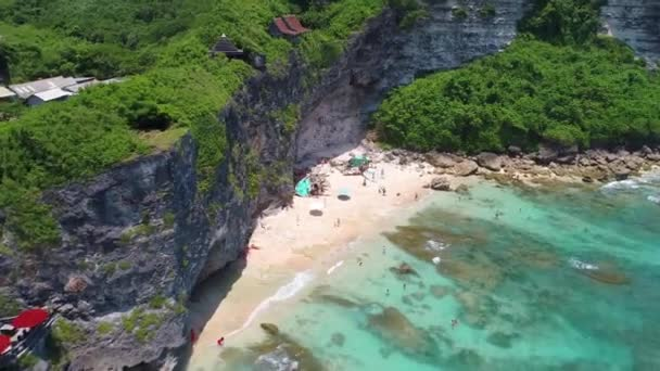 Flight along the beautiful coastline, turquoise ocean and the waves crashing on the rocks. Surfers catch the waves on reef. Garbage in the sea. Bali, Uluwatu beach.