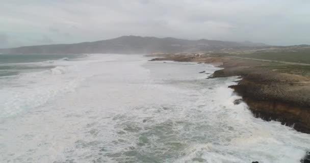 Horní pohled na moře skalnaté pobřeží a velké vlny. Maják na břehu a velká vlna.Dramatický pohled na atlantické pobřeží. Dron letící pod skalnatým atlantickým pobřežím, útesy a velkými vlnami.