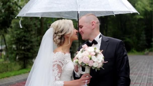 glückliche Braut und Bräutigam in einem verregneten Hochzeitstag versteckt sich vor Regen
