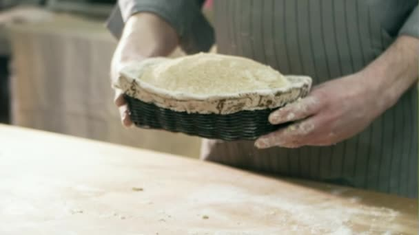 Baker man holding rustic organic loaf of bread in hands before baking in the oven - rural bakery. Slow motion.