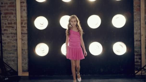 Dětská modelka chlapu molo v růžových šatech a pózování před kamerou