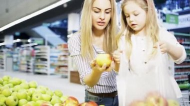 A little girl with her mother buys apples in a supermarket