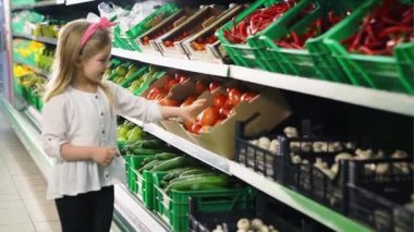 The young girl chooses a tomato in a supermarket and is happy when he finds it