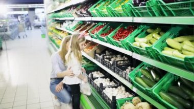 A woman with a young girl chooses mushrooms on the shelves of the supermarket