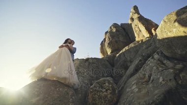 Newly married couple standing on stone