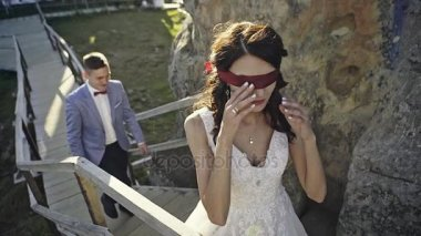 Blindfolded bride going upstairs
