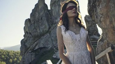 A mysterious beautiful bride with blindfolds awaits her fiancee on the background of the sunset between the magical rocks