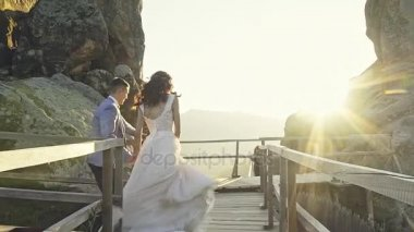 Wedding couple happily run by holding hands in the mountains with stunning views