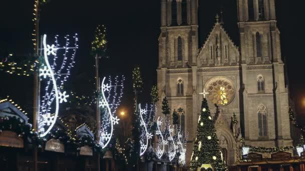 spravedlivé suvenýr a krásně zdobené vánoční strom na náměstí náměstí míru pozadí majestátní budova kostela St. Ludmila
