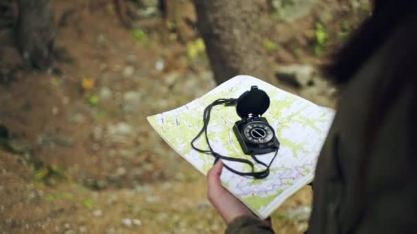 Female traveler holding a compass and looking for direction navigation, search path or road.
