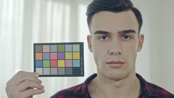 Young man holding up a color checker card